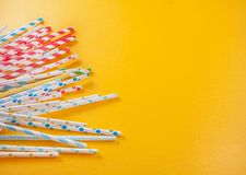 Drinking paper colorful straws for summer cocktails on yellow background with copy space. Top view. Drinking paper colorful straws for summer cocktails on yellow royalty free stock photo