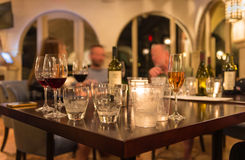 Drinking party. A dark brown table with number of wine and many nearly empty drinking glasses and wine bottles on top also small group of blurry people talking Stock Photography