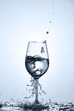 Drinking pure water poured into a transparent wineglass standing on the glass with droplets against light background. Stock Photo
