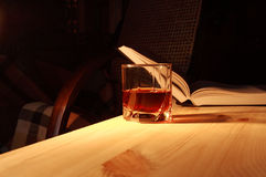 Drinking And Reading. Glass of drink on wooden table on backgound with open book and home interior Royalty Free Stock Photography