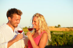 Drinking red wine couple at vineyard. Drinking red wine couple in love. Happy people drinking rose wine alcohol laughing in summer vineyard Royalty Free Stock Images