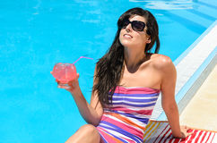 Drinking refreshment at poolside Stock Photo