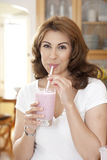 Drinking a Smoothie. Woman drinking a fruit smoothie through a straw in kitchen setting Royalty Free Stock Image