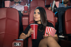 Drinking soda and eating popcorn at the movies. Portrait of a beautiful women eating some popcorn and drinking soda while sitting in a movie theater Royalty Free Stock Photography