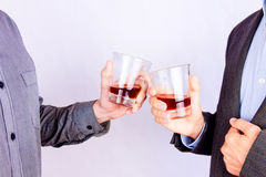 Drinking some alcohol. Close-up of men`s  hands cheering up with glasses of whisky Stock Images