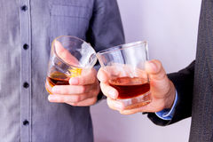 Drinking some alcohol. Close-up of men`s  hands cheering up with glasses of whisky Royalty Free Stock Photo