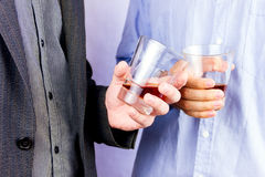 Drinking some alcohol. Close-up of men`s  hands cheering up with glasses of whisky Stock Photography