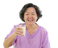 Drinking soy milk. Asian senior woman drinking a glass of soy milk over white background Royalty Free Stock Photo