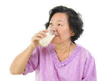Drinking soy milk. Asian senior woman drinking a glass of soy milk over white background Stock Photos