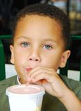 Drinking from Straw. This very attractive young boy is at a local cafe drinking from a straw Stock Photography
