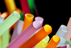 Drinking straws on a dark background. Bunch of drinking straws in bright pastel colors on a dark background Royalty Free Stock Images
