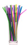 Drinking straws in glass over white. Bright plastic drinking straws, in glass Royalty Free Stock Images