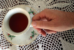 Drinking Tea. At a table dressed with a crocheted lace tablecloth Stock Photo