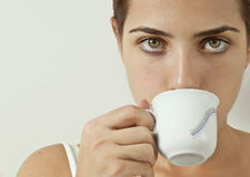 Girl Drinking Tea. A beautiful young lady drinking tea or coffee. She is looking directly at the camera Royalty Free Stock Photos
