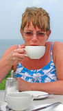 Drinking tea coffee alfresco at beach. Photo of woman model drinking tea or coffee alfresco by the beach Royalty Free Stock Photography