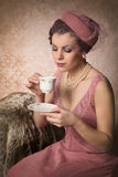 Drinking tea Gatsby style. Attractive vintage 1920s lady with flapper dress and matching hat drinking tea stock images