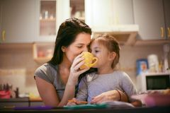 Drinking tea with mom is fun. Little girl. Drinking tea with mom is fun. Little girl with her mother royalty free stock photography