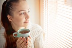 Drinking tea sitting on the window of Caucasian beautiful middle-aged woman with red hair, toning.  stock image