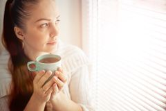 Drinking tea sitting on the window of Caucasian beautiful middle-aged woman with red hair, toning.  royalty free stock photography