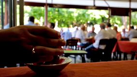 Drinking tea in turkish cafe. The hot black tea in the popular tea house in old town, famous among local seniors, relaxing on the summer terrace and playing tile stock video