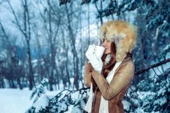Drinking tea in the winter park. Calm contented woman gladly drinks hot coffee among snow-covered trees, enjoys the winter holidays walking in the park stock photography