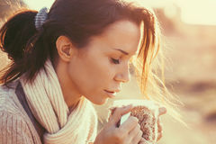 Drinking tea. Woman wearing warm knit clothes drinking cup of hot tea or coffee outdoors in sunlight Royalty Free Stock Photo