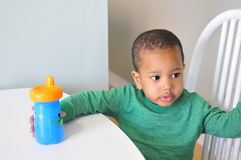 Drinking time from cup. Young black boy at dining table holding blue cup with drink for himself Stock Photography