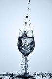Drinking transparent water is poured into a wineglass standing on the glass against light background. Royalty Free Stock Images