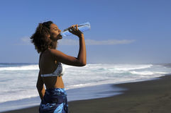 Drinking water 1. Young mixed girl drinking water at the beach Royalty Free Stock Images