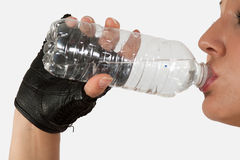 Drinking water. Close up of a woman hand holding and drinking from a clear water bottle stock images