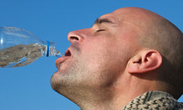 Drinking water. Man drinking fresh mineral water from bottle Stock Image