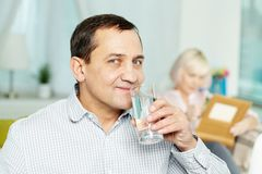 Drinking water. Portrait of happy senior men drinking water from glass and his wife reading book behind Royalty Free Stock Photography
