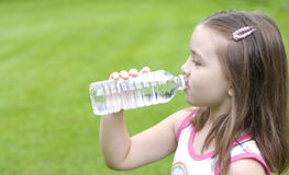 Drinking water. A cute little girl drinking bottled water on a hot summer day Stock Photography
