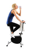 Drinking water on bike. Slim fitness girl drinking mineral water while riding on a training exercise bike Stock Photography