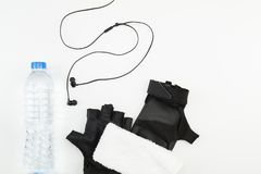 Drinking water bottle, black gloves, white towel and headphone on white background Stock Photo