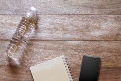Drinking water bottle, smartphone and notebook on vintage wooden background stock images
