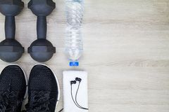Drinking water bottle, sport shoes, dumbbells, white towel and headphone on wooden background Stock Photos