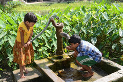 Drinking Water. Children drinking water from a tube-well in the remote village of India Royalty Free Stock Photos