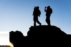 Drinking water climbers on summit. Victory at the peak of happiness Stock Photos