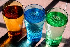 Drinking Water in Colorful Glasses. Three color-tinted glasses filled with drinking water Stock Images