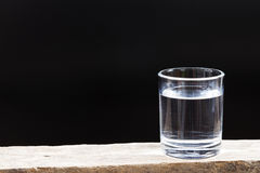 Drinking water on a dark background. Stock Photos