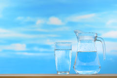Drinking water. Fresh and clean drinking water in jug and glass on sky background Royalty Free Stock Photos