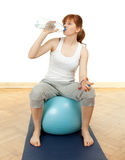 Drinking water girl sitting on blue ball Royalty Free Stock Images