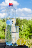 Drinking water in a glass from a bottle on a nature background Stock Photo