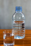 Drinking water in glass and plastic bottles on a wooden table. Stock Photography