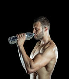 Drinking water in gym. Young adult man drinking water in gym Stock Image