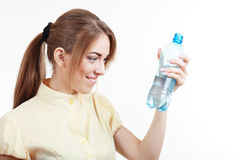 Drinking water nutrition. Woman reading lable bottle of pure still drinking water nutrition facts. Female hold in hand sparkling mineral bottled water isolated royalty free stock image