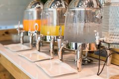 Drinking cornet of buffet hotel restaurant. Drinking water, orange and pineapple juice in ice tank at hotel buffet restaurant table. cold drink near variety of Stock Photo