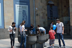 Drinking water. People deinking water from the drinking fountain on the Republic square, Erevan (close to the History museum of Armenia Stock Image