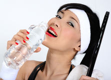 Drinking water after playing squash. Young asian woman drinking water after playing squash Royalty Free Stock Images